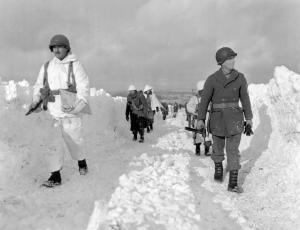 American infantrymen of an armored division march on a snow-covered road southeast of Born, Belgium, on Jan. 22, 1945. (ASSOCIATED PRESS)