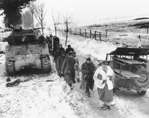 German captives walk past a disabled tank as they are led into captivity by U.S. troops, on Jan. 25, 1945, north of Foy, Belgium, in the final days of the Battle of the Bulge. (ASSOCIATED PRESS)