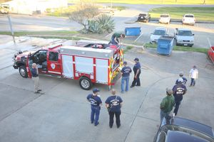 Needville firefighters gather around their new rescue truck